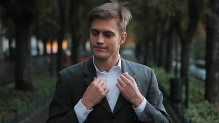 определенный : Portrait of young successful confident businessman straightens clothes in the city. Man in a business suit in the autumn street. Slow motion. Smiling happy person portrait.