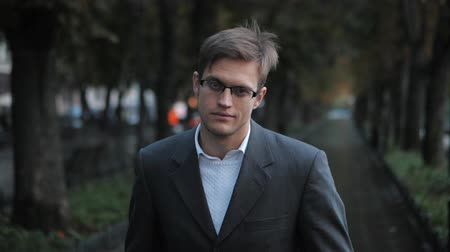 определенный : Portrait of young successful confident businessman in the city. Man in a business suit and glasses in the autumn street. Slow motion. Portrait of handsome guy.