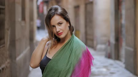 arka görünüm : Front view of sexy elegant woman walking in the old european city. Attractive lady in long black dress, colorful scarf and heels in gothic quarter of Barcelona. Slow motion.