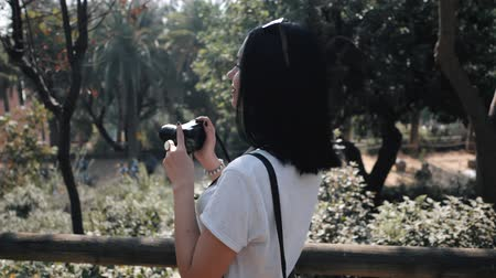 photojournalist : Beautiful young tourist brunette woman takes photos of nature in Barcelona park on small professional digital camera. Travel concept. Dolly shot, Slow motion