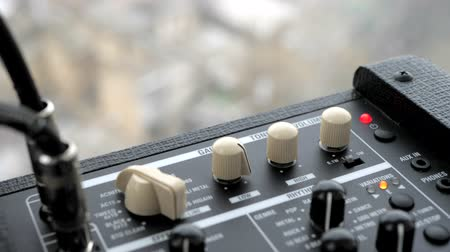 pohárek : Cranking up the volume knob. Male hands twist tumblers on control panel of guitar amplifier. Amp close up