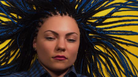 blue braid : Beautiful young girl with african blue braids is surprised and looks at the camera. Stop motion animation. Woman on bright yellow background. Dyed Hair moves. Hipster.