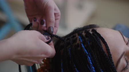 blue braid : Process of weaving African braid with kanekalon. Small African braids with blue artificial strands. Topical hairstyle - bright braids. Master plaits braids with blue artificial strands.