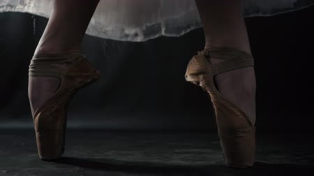 kültürlü : Close up of ballet dancer as she practices exercises on dark stage or studio. Womans feet in pointe shoes. Ballerina shows classic ballet pas. Slow motion. Flare, gimbal shot.