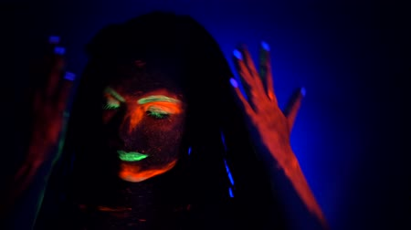 korhadt : Fashion model woman with braids dancing in neon light. Fluorescent makeup glowing under UV black light. Night club, party, halloween psychedelic concepts.