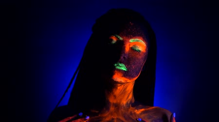 pankáč : Girl sexy smears and rubs fluorescent paint on her body. Dye glowing under UV black light. Woman with braids in neon light. Night club, party, halloween psychedelic concepts.