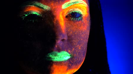 pankáč : Close up portrait of fashion model woman with braids in neon light. Fluorescent makeup glowing under UV black light. Night club, party, halloween psychedelic concepts.