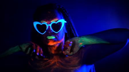 vinil : Fashion sexy dancer with heart shaped glasses in neon light. Fluorescent makeup glowing under ultraviolet light. Night club, party, psychedelic concepts. Mysterious woman with UV painting Stock Footage