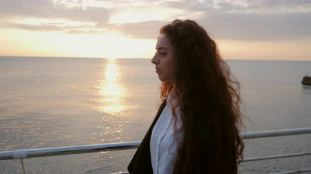 спокойный : Beautiful girl with curly long hair walking towards the camera on sunny spring sea beach. Young stylish business woman in fashion black coat and white shirt on wooden embankment near ocean.