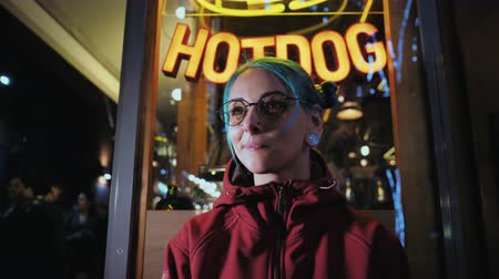 pankáč : Hipster girl with blue dyed hair. Woman with piercing in nose, lenses, ears tunnels and unusual hairstyle stands at night illuminated city near neon showcase with hot dog Dostupné videozáznamy