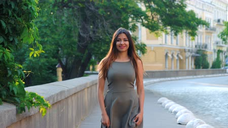 seçkinler : Pretty lady walking on camera and turning around with smile. City street style portrait. Woman walking alone. Attractive girl with oriental face in short dress at summer season.
