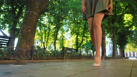 элита : Sexy legs with high beige heels walking in park of city. Woman walking on boulvard alone. Attractive girl in short dress at summer season. Slow motion.