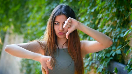 downwards : Young beautiful woman standing on green foliage background expressing discontent and showing thumb down gesture at camera. Portrait of girl with sign of dislike Stock Footage