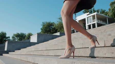 элита : Sexy legs with high beige heels goes down the stairs of big city. Roamntic woman walking on boulvard alone. Attractive girl in short dress at summer season. Slow motion.