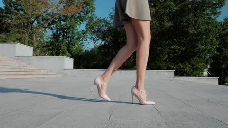 seçkinler : Sexy legs with high beige heels goes down the stairs of big city. Roamntic woman walking on boulvard alone. Attractive girl in short dress at summer season. Slow motion.