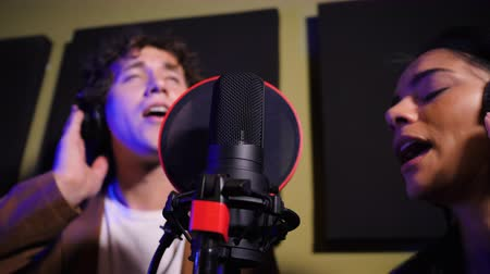 microphone : Two young singers performing their song in record studio. Professional musician duet recording new album CD. Beautiful couple working together. Slow motion. 4k