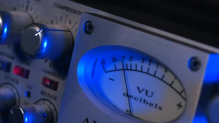 editor : Old Reel to Reel Tape recorder close up. Shallow DOF of standard volume indicator scale. Vintage audio device analog VU meter. Recording studio. Blue neon light.