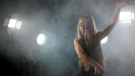 poddasze : Professional ballerina dancing ballet in spotlights smoke on big stage. Beautiful caucasian young girl with long hair wearing black tight dress on floodlights background.