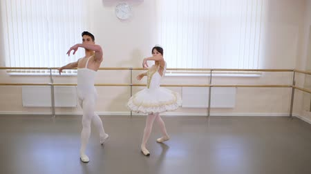 pirouette : Rehearsal in the ballet hall or studio with minimalism interior. Young professional sensual dancers couple in beautiful costumes dancing together. Slow motion. Stock Footage