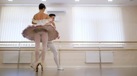 fegyelem : Young man practicing in classical ballet with beautiful woman in white tutu dress in the gym or ballet hall. Choreographer discuss movements of dance with his student. Slow motion