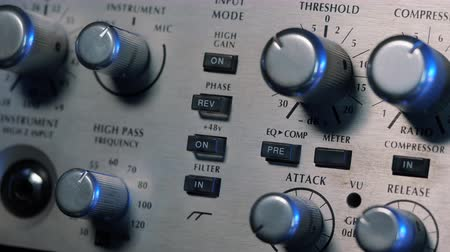 véu : Adjustable handles on the compressor panel in professional recording studio. Natural light. Sound mixing concept. Dolly shot. 4k. Stock Footage