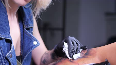 adorno : View of professional blonde tattoo female master is painting with black ink, making cover. Works in sterile latex gloves with handmade rotor gun machine in studio. Slow motion. 4k