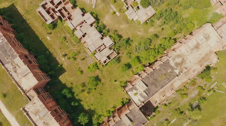 blight : Flying above old abandoned construction. AERIAL: Flight over unfinished high-rise building with apartments. Drone view. Summer season. Abandoned city after disaster. HD footage.