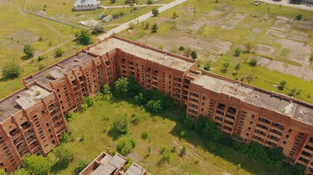 abandonment : Flying above old abandoned construction. AERIAL: Flight over unfinished high-rise building with apartments. Drone view. Summer season. Abandoned city after disaster. HD footage.