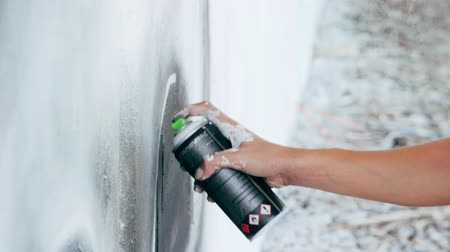 ghetto streets : Graffiti Artist Painting On The Street Wall. Female hand with aerosol spray bottle spraying with colorful paint, Urban Outdoors Art Concept. Slow motion. Close up view. Stock Footage