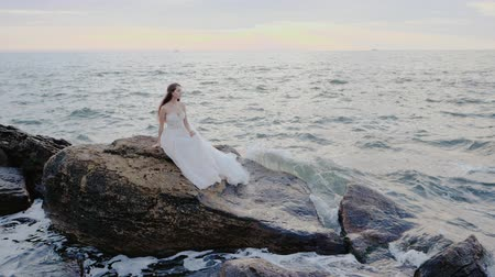 pulverização : Girl in wedding luxury dress posing on sea shore. Bride sits on rocks. Beautiful waves near to her. Woman enjoying happy moments with nature. Sunrise or sunset time. Slow motion.