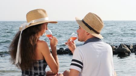 жених : Young beautiful couple drinking wine on date together near sea on the beach. Boyfriend and girlfriend on picnic. They love each other. Relationship concept. Slow motion Стоковые видеозаписи