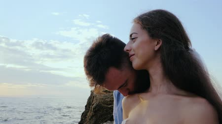 darling : Beautiful young wedding couple standing on sea shore with rocks. Newlyweds spend time together: embrace, kiss and care for each other. Love concept. Stock Footage