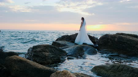 długi : Girl in wedding luxury dress posing on sea shore. Bride on a rocks. Beautiful waves near to her. Woman enjoying happy moments with nature. Sunrise or sunset time. Slow motion.