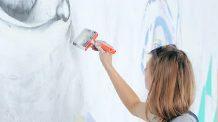 chmiel : Graffiti Artist Drawing face of beautiful woman with paint on Street Wall. Female working with brush. Urban Outdoors Art Concept. Slow motion.
