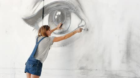 произведение искусства : Graffiti Artist Drawing face of beautiful woman and eye with paint on Street Wall. Female working with brush. Urban Outdoors Art Concept. Slow motion.