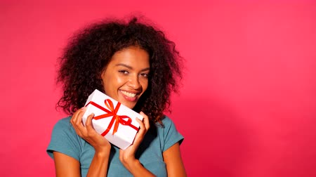 přítomný : Pretty african-american young woman holding gift box with red ribbon and bow on pink wall background. Girl smiling, she is happy to get present. 4k