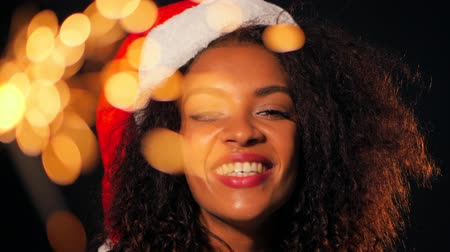 na zdraví : African-american young woman in party dress holding bengal sparklers fire and dancing on black lights background. Girl in Santa hat on New Year or Christmas. Slow motion