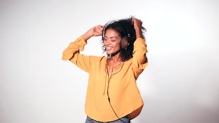 camera move : Attractive african-american young woman listening to music with headphones and dancing on white wall background. Girl in yellow clothes. Studio footage. Music concept. Slow motion