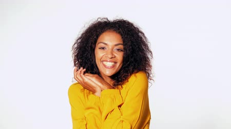 biust : Beautiful african american woman with afro hair in yellow wear smiling, pleasantly surprised to camera over white wall background. Cute mixed race girls portrait with amazement