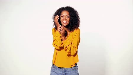 biust : Pretty african woman in yellow wear learned pleasant news and is happy with what was heard over white background. Cute mixed race girl shocked, saying WOW. 4k
