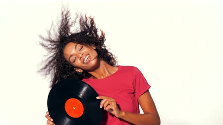 afro amerikan : Young pretty african american woman in red top enjoying and dancing with vinyl records at white background. Modern trendy black girl with afro hairstyle. 4k Stok Video