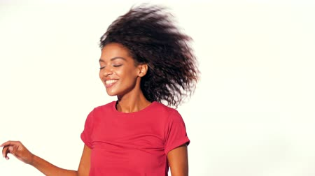 afro amerikai : Young attractive african american woman in red top enjoying life and dancing at white background. Modern trendy black girl with afro hairstyle. 4k