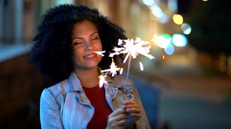 mischief : Young beautiful woman with very curly afro hair dancing with bengal fire at night illuminated street. Unusual trendy girl with sparklers. Holiday concept. 4k footage