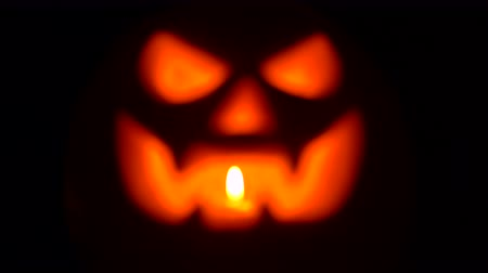 homály : Pumpkin with light inside in darkness. Blurry background. Terrifying symbol of Halloween - Jack-o-lantern. 4k Stock mozgókép