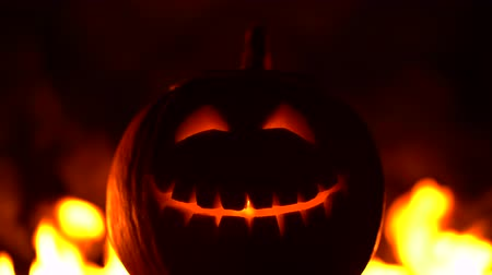ijesztő : Black smiling happy carved halloween pumpkin against of fiery explosion background. Glowing face trick or treat. Symbol of All Hallows Eve or All Saints Eve. 4k Stock mozgókép