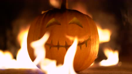uğursuz : Smiling happy carved halloween pumpkin against of fiery explosion background. Glowing face trick or treat. Orange squash in the center of the fire frame. 4k
