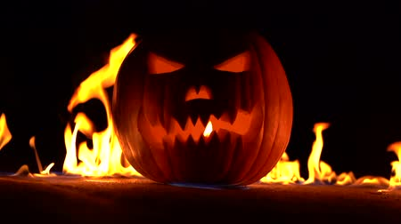 firebox : Horrible pumpkin as head of jack-o-lantern with carved eyes and wicked smirk in burning hell. Scary symbol of Halloween in fire explosion. Slow motion. Stock Footage