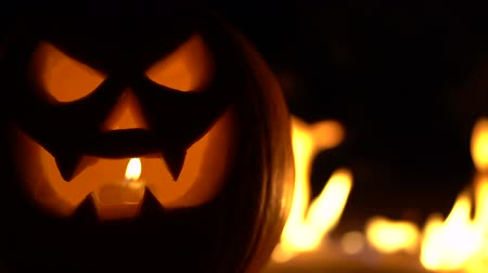 carving : Dreadful mad pumpkin as head of Jack-o-lantern with carved eyes and wicked smirk on burning hell fire. Scary symbol of Halloween, All Hallows Eve. Gourd on left side. Slow motion. Stock Footage