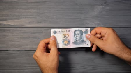 büntetés : Stop animation. Ten yuan turns into hundred dollars banknote. Chinese currency is being transformed into the US. Magician. Capital increase. Business and finance concept.
