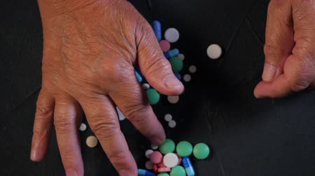 adagolás : Grandmother counts multicolored tablets on black table at home. The concept of old age, medication, treatment. Close-up of hands with wrinkles. Slow motion